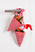 Small Christmas bag with branch and candy cane hanging on door handle on white background