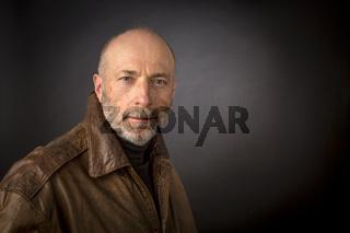 headshot of older man in leather jacket