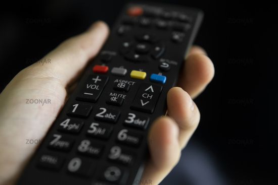 Close up on a man's hand with the remote control want switch on the TV and presses the button on the remote control. Remote control in hand closeup.