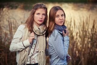 Two young fashion girls in white shirt and scarf walking outdoor