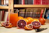 Glass of juice, knife and cut red oranges on a light wooden table. Blurred book shelves in the background.