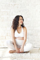Beautiful pregnant woman stretching and practicing yoga at home
