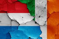 flags of Luxembourg and Ireland painted on cracked wall