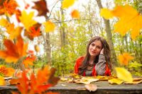 Beautiful romantic girl in park autumn scenery, sitting down at a wooden table and looking at the camera, blurred yellow leaves are falling in the foreground. Close-up landscape shot in natural light