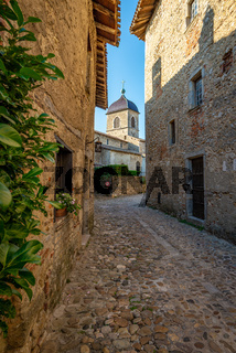 Narrow street framing a view of the church steeple, Perouges, F