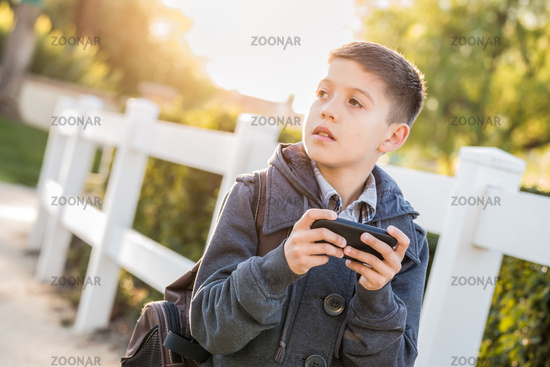 Concerned Young Hispanic Boy Walking With Backpack Holding Cell Phone