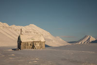 Small cabin in the arctic winter landscape with snow covered mountains on Svalbard, Norway
