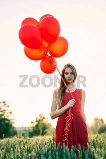 Young beautiful woman in red dress posing in green field with red balloons on sunset