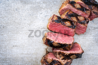 Barbecue wagyu roast beef sliced as top view on a gray board with copy space left