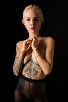 Tattooed blonde wearing only stockings