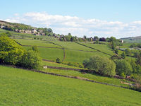 sunlit spring countryside with hillside fields and stone walls with the village of old town in calderdale west yorkshire