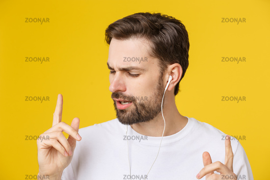 Handsome of a young man enjoying music over yellow background.