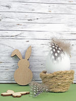 Ostern Hintergrund mit Osterei, Osterhase und Schmetterling auf grün vor Holz