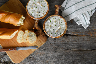 Top view of two bowls of homemade Clam Chowder with fresh baked loaf of bread. Horizontal with copy space.
