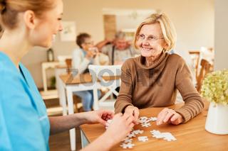 Demente Seniorin im Pflegeheim spielt Puzzle