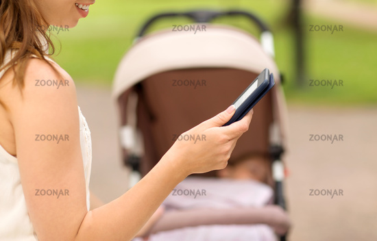 mother with stroller reading internet book at park