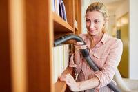Putzfrau beim entstauben von Bücherregal
