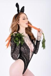 Schoner, grosser, schlanker, vollbusiger Rotschopf als unartiger Osterhase, mit Karotten