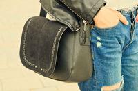 Young woman hold yoyr hand in pocket wih black handbag on her shoulder