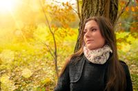 Close-up shot of a beautiful romantic girl with perfect skin and complexion, in a park autumn scenery, sitting down and leaning against a tree, enjoying the warm sunny day. Natural light portrait