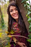 Close-up portrait of a gorgeous romantic young woman with beautiful long brown hair, in autumn park outdoors scenery, looking at the camera and smiling happy. Natural light, retouched, vibrant colors