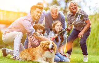 Große Familie macht Selfie im Garten mit Hund