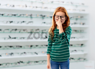 red haired student girl in glasses at optics store