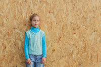 Little girl in blue sweater stands near wall