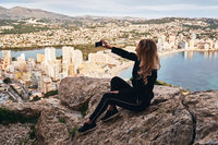 Blonde woman seated on stone rock posing makes selfie picture use phone capture moment climbed up on Penon de Ifach rock in natural park. Calpe spanish townscape on background, Costa Blanca, Spain