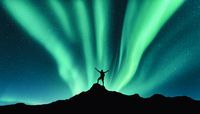 Northern lights and silhouette of standing happy man. Aurora