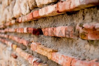 Old brick wall of red bricks. Ancient fortress wall. Medieval Roman citadel fortress. Old red bricks and mortar, grunge background.