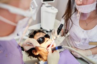 Zahnarzt mit Bohrer und seinem Team