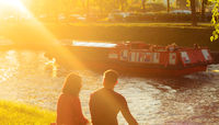 At sunset a lovely couple sits on the bank of a river canal in a city park and talks each other.The canal floats pleasure boat.Good Summer weekend.