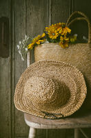 Closeup of sunflowers in straw purse on chair