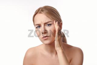 Hübsche junge Frau schaut skeptisch in den Spiegel