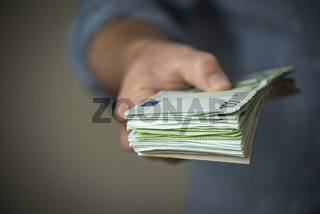 Hand giving a Stack of Euro Bills
