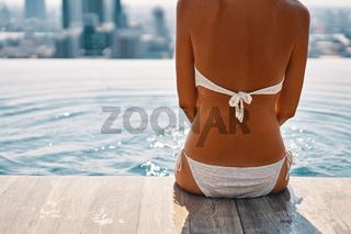 Back view of slim beautiful woman relax in swimming pool