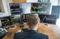 Over the shoulder view of stock broker trading online.