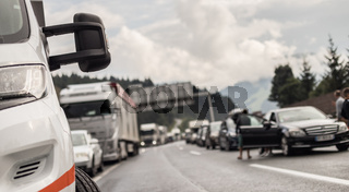 Typical scene on European highways during summer holiadays rush hour. A traffic jam with rows of cars tue to highway car accident. Empty emergency lane. Shallow depth of field
