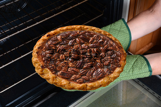 Closeup of a woman taking a fresh baked Pecan Pie from the oven. Horizontal showing the womans hands in oven mitts only.