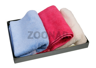 Colored terry new bath towels in a cardboard box isolated