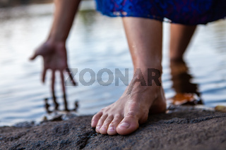 Young woman walks out of the water while touching the water with her hand