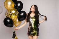 Elegant brunette lady with long hair in sparkling cocktail dress with air balloons.