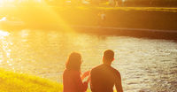 At sunset a lovely couple sits on the bank of a river canal in a city park and talks each other.Good Summer weekend.
