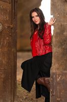 Fashion concept portrait of a gorgeous young woman sitting in a door of an old abandoned building and looking at the camera, in red leather jacket and black skirt outfit. Retouched, vibrant colors