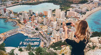 Girl climbed up on Penon de Ifach rock. Enjoy view of city from top, stand on peak of mountain takes photo of cityscape and scenery. Tourism, landmark, tourist capture moment concept, Calpe, Spain