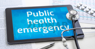 The word Public health emergency on the display of a tablet