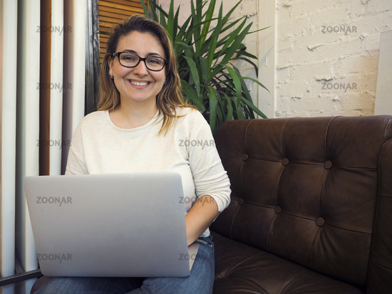 Beautiful mixed race woman sitting in a coffee shop using her laptop