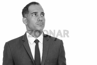 Mature handsome Persian businessman thinking in black and white