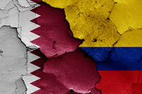 flags of Qatar and Colombia painted on cracked wall